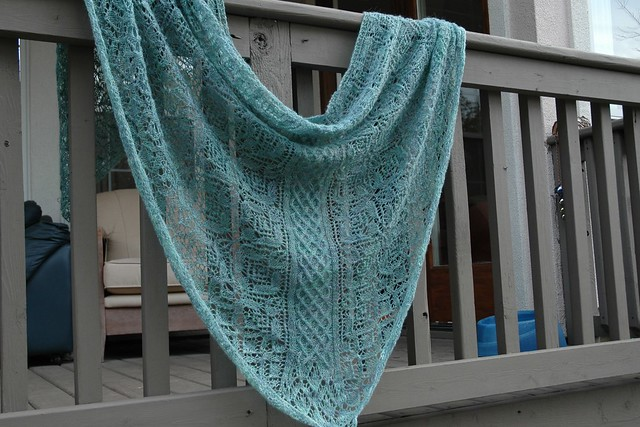 light blue lace shawl draped over a porch rail
