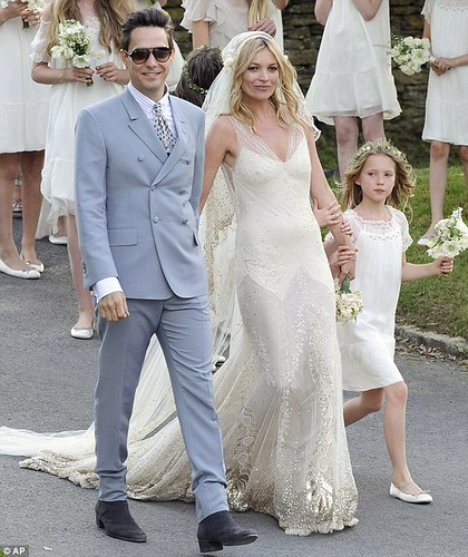 The couple strides into the village after marrying in a Church of England ceremony