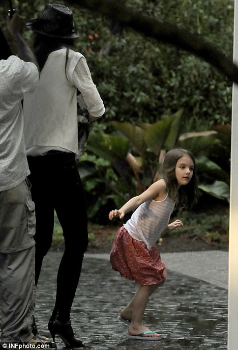 Rain dance! Smiling Suri Cruise larks around in miserable Miami  1