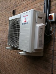 Air source heat pump outdoor unit mounted on a wall at customers house