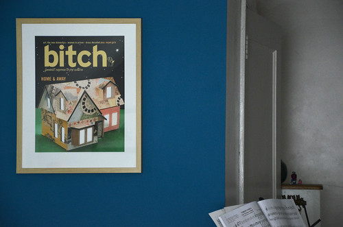 Home and Away print hanging on a blue wall. The print shows a model of a house with a light on inside