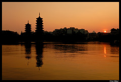 Guilin sunset (Dan Wiklund) Tags: china sunset orange sun lake reflection skyline pagoda cityscape guilin buddhist d200 pagodas silhuette guanxi twinpagodas 2011 gulin shanlake sunpagoda moonpagoda pagodamoon