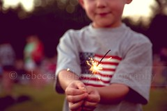 Little boy holding a 4th of July sparkler (Rebecca812) Tags: family blue boy red usa white cute smile childhood vintage stars outside happy holding child fireworks dusk stripes flag son excited patriotic retro celebration american americana sparkler selectivefocus incidentalpeople whatgettywants heritage2011