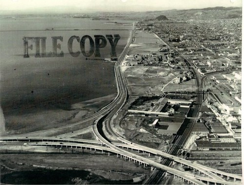 <em>Aerial photo from 1944 of the Eastshore Highway with the Bay Bridge/Oakland interchange in the foreground. Completion of the four-lane road in 1937 seems to have been the catalyst for Albanys original slogan.&#8221; width=&#8221;450&#8243; height=&#8221;341&#8243; /><p class=
