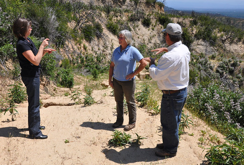 A sign language interpreter facilitates communication as Bob Bailey explains how soil erosion concerns on an access road might be addressed.