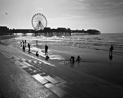 a place in the sun (Blackpool) (Andre Delhaye) Tags: uk shadow sea england people sun white seascape black reflection beach water silhouette clouds dark landscape concrete lumix pier waves photographer seagull steps andre panasonic gb ferriswheel seashore blackpool 43 csc m43 mft mirrorless delhaye micro43 microfourthirds 43 wwwandredelhayecom wwwandredelhayenet lumixg3 dmcg3 panasonicg3 andredelhayephotographer
