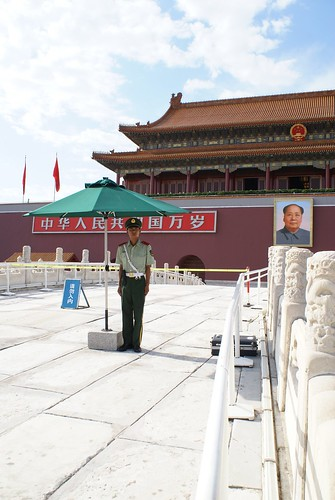 Soldier in front of Forbidden City with his own umbrella