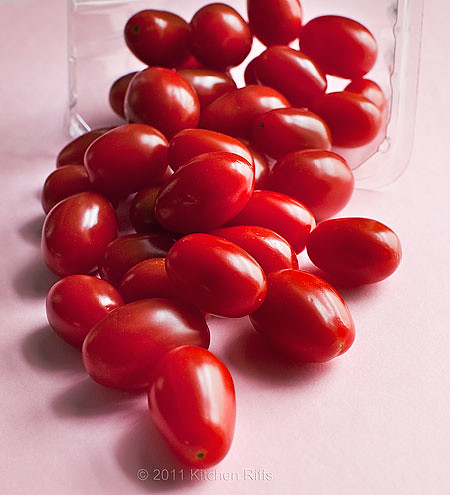 grape tomatoes tumbling out of plastic 1-pint container