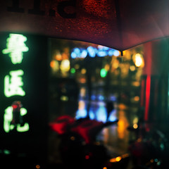 Umbrella (Jonathan Kos-Read) Tags: china street red storm green wet water rain yellow night umbrella square 50mm asia neon bokeh beijing scooter sanlitun drizzle chinesecalligraphy chinesecharacters redumbrella goldenratio barstreet nikond700 bardistrict neonreflections