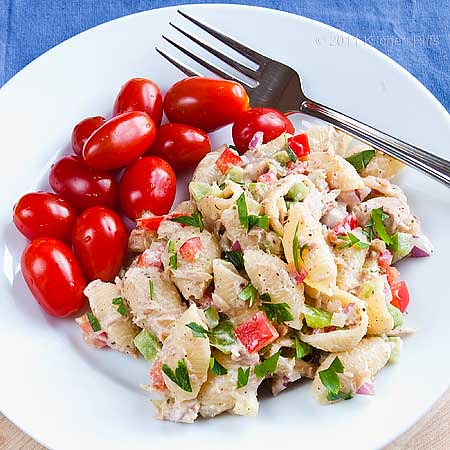 Tuna Pasta Salad on plate with grape tomatoes, overhead view
