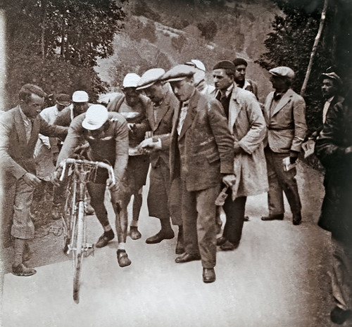 André Leducq, leader of the Tour on stage 16, fell heavily on the descent of the Col du Galibier, broke his bike and lost 14 minutes. Despite this potential disaster, Leducq got a replacement bike and, with the help of his team, made it back to the front of the race incredibly winning the stage into Evian on Lake Geneva, saving his Tour. This image captures the moment Leducq remounts after his fall, blood visible on his left leg.