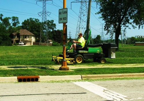 A John Deere riding mower and operator at work. Morton Grove Illinois USA. Early August 2011. by Eddie from Chicago