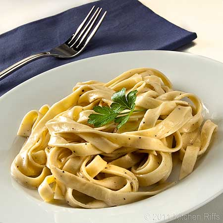 Fettuccine Alfredo on white plate with napkin and fork in background