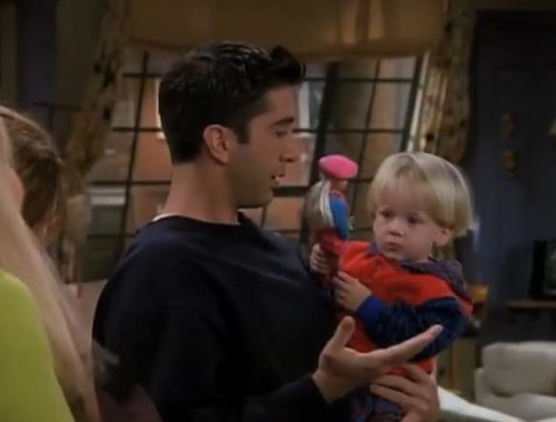 a screencap of Ross Gellar holding and looking incredulously at his young blonde son who is holding a Barbie doll
