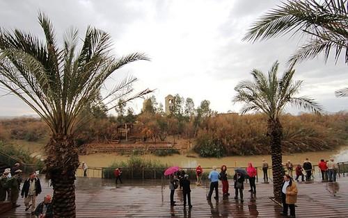 Peregrinos en el estrado sobre el rio Jordan en el lugar de bautismo de Jesús