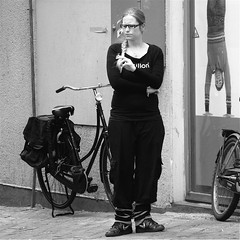 HATE YOUR CIGARETTE! (Akbar Simonse) Tags: street people urban bw holland netherlands girl monochrome bicycle square glasses zwartwit candid streetphotography denhaag smoking spectacles thehague braid fiets streetshot straat straatfotografie straatfoto straatfotograaf dedoka akbarsimonse hateyourcigarette