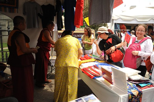 Monks working their booth, Tibetan woman in forground is wearing a two piece patterned yellow Tibetan chuba of contemporary design, tent market, Kalachakra for World Peace, Happy Birthday to the Dalai Lama Parade, Washington D.C., USA by Wonderlane