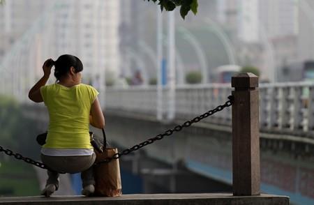 一女子坐在铁栏的围栏上