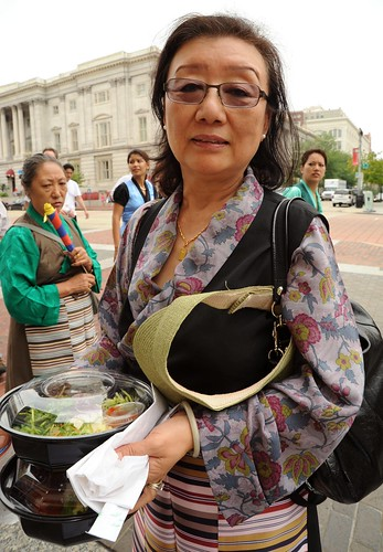 Mrs. Yuthok, carrying a salad lunch, wears a black chuba and restrained artistic floral blouse, with apron, Kalachakra for World Peace, Happy Birthday to the Dalai Lama Parade, Washington D.C., USA by Wonderlane