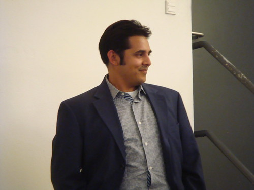 A close-up photo of Jigar Mehta listening with a shy smile to the introduction about his presentation.