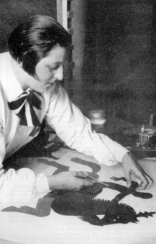a black and white photo of Lotte Reiniger at her desk working on a shadow puppet