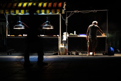 Nuts seller (Elios.k) Tags: street light shadow people man motion color silhouette horizontal night walking outdoors moving movement corn warm market walk working nuts stall tent greece getty thessaloniki seller subgetty