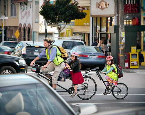 A family outing with four on a bike at 16th and Valencia St, along a new bike corridor created by the city of San Francisco