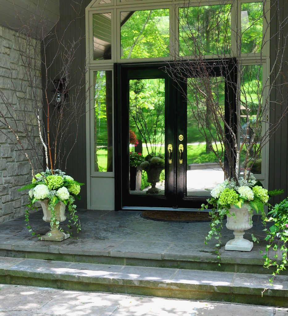 White urns overflowing with hydrangea, hosta, ivy and birch branches welcome guests at the front entrance