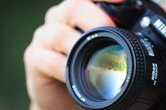 Watching the World through a lens (Porfidax) Tags: lens flickr addiction spherical aberration flip landscape hand photographer color green blue black bokeh nikon d5000 d90 nikkor 85mm sigma 70300 nikonclubit