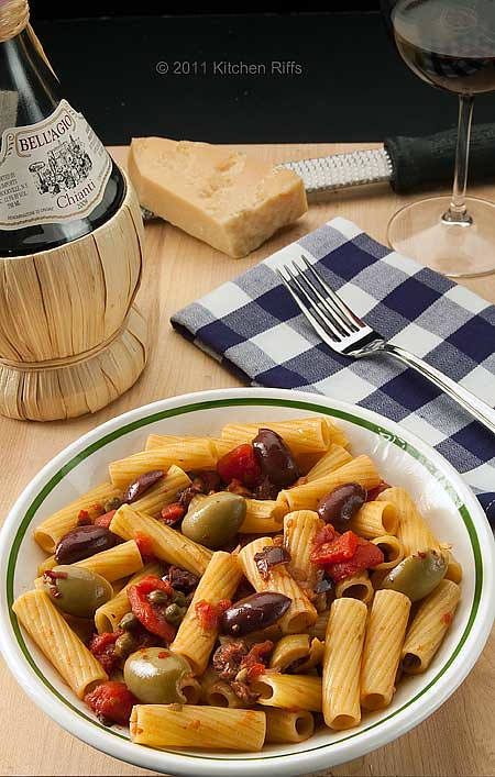 Pasta Puttanesca in bowl with straw-covered wine bottle and Parmesan cheese in background