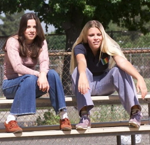 Lindsay and Kim, a white teenage girl with blond hair, sit on the bleachers