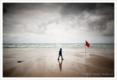 Whitesand Bay, Sennen Cove (Andy Stafford) Tags: boy red reflection beach wet clouds walking sand cornwall flag overcast stormy whitesandbay sennen sennencove