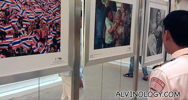 A security guard checking out a photo exhibition in Siam Paragon, Bangkok