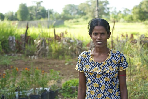 A benificiary in front of her home garden in a villiage by Trincomalee