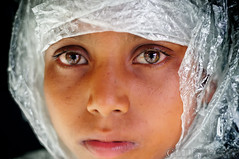 On rain and raincoats.. (Neerod [ www.shahnewazkarim.com ]) Tags: morning light boy water look rain drops kid fisherman eyes child head coat warp warped plastic stare raincoat alim maowa