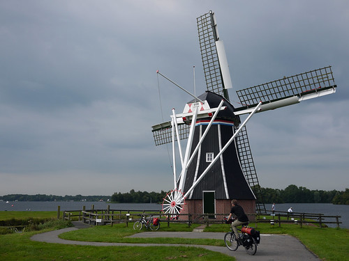 Andrew cycling past a windmill