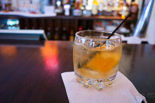 Glass of rum on the rocks with a thick slice of orange at Salute! NYC