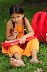 Little girl (Pixmac_at) Tags: red summer orange green smile grass smiling children daylight spring sitting drawing sit frontview goodtime schoolbag realpeople exterierscene