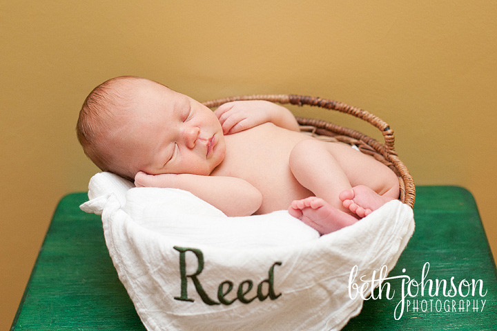 newborn baby boy with his name on his blanket in basket