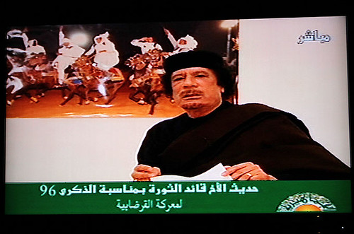 Poster Libyan revolutionary leader Muammar Gaddafi speaking on television in the North African oil-rich state. Libya has fought off an imperialist onslaught for the last six months. by Pan-African News Wire File Photos