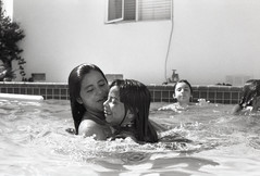 Swimming Lesson (On a sabbatical) Tags: summer blackandwhite bw pool kids swimming children iso200 blackwhite holding thoughtful 35mmfilm innocence teaching lesson kindness moment rare hold pushprocess rarity canoneosrebel thoughtfulness pushed1stop adoxchs100 1stop 50mmf14usm june2011 17thletterphotography