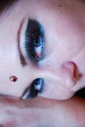 A white woman with Cleopatra-like blue eye makeup and a jewel on her forehead.