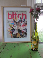 Genesis print in a frame sitting on a green table next to a vase of flowers. The print features origami folded into a spiky ball.