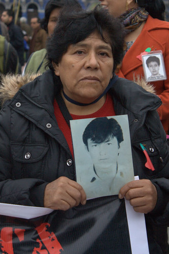 La Cantuta relative holding a picture of her son