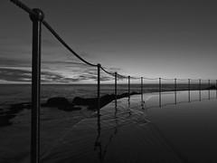 Serenity (Willieozify) Tags: blackandwhite bw silhouette sunrise dawn serenity vignetting tidalpool 43 calmwater reflectiononwater cotcmostfavorited waterpattern waterripple steelfencing flickrmassageoct2011