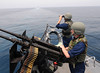 Sailors man a .50-caliber machine gun during a security watch aboard USS Truxtun