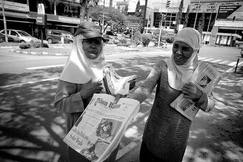 Selling Newspapers by the traffic junction