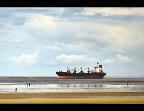 Big ship sails into the river Mersey watched over by the Ironmen of Crosby by Ianmoran1970