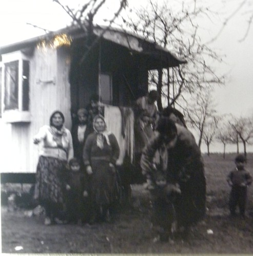Photograph of a traditional Roma family outside of their caravan.