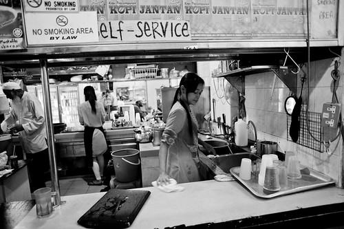 A lady clearing up the counter after the stall closing time.